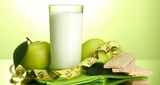 Домашний кефир из закваски живой баланс в стакане с зелеными яблоками и хлебцами на зеленой салфетке с мерной лентой