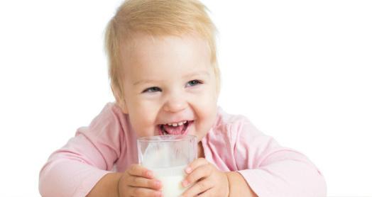 Малыш пьет из прозрачного стеклянного стакана кефир из закваски живой баланс