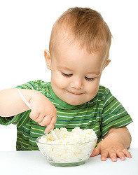 малыш кушает творог из закваски живой баланс в стеклянной пиале пластмассовой ложкой