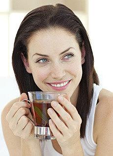 темноволосая девушка пьет иван-чай живой баланс из стеклянной чашки