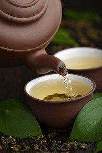 заваренный иван-чай наливают из керамического коричневого чайника в чашку