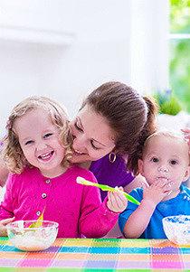 мама с детьми за столом кушают йогурт из закваски живой баланс из белых пиал ложками