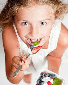 девочка кушает йогурт из закваски живой баланс с ягодами