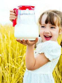 кефир из закваски живой баланс в стеклянном кувшине в руках девочки в поле пшеницы